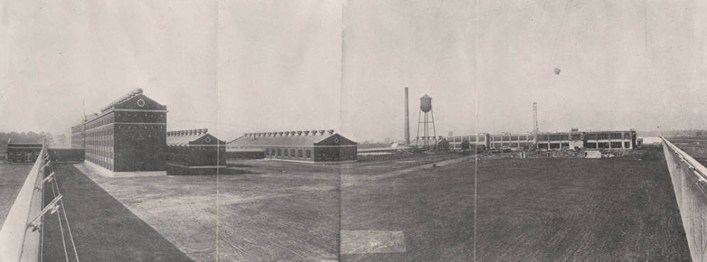 A wide view, black and white photograph showing a prison yard, brick prison buildings, and water tower inside tall fences.