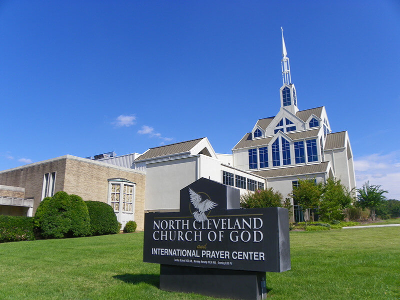 Photograph of North Cleveland Church of God, a large white building with tall windows and a white steeple.
