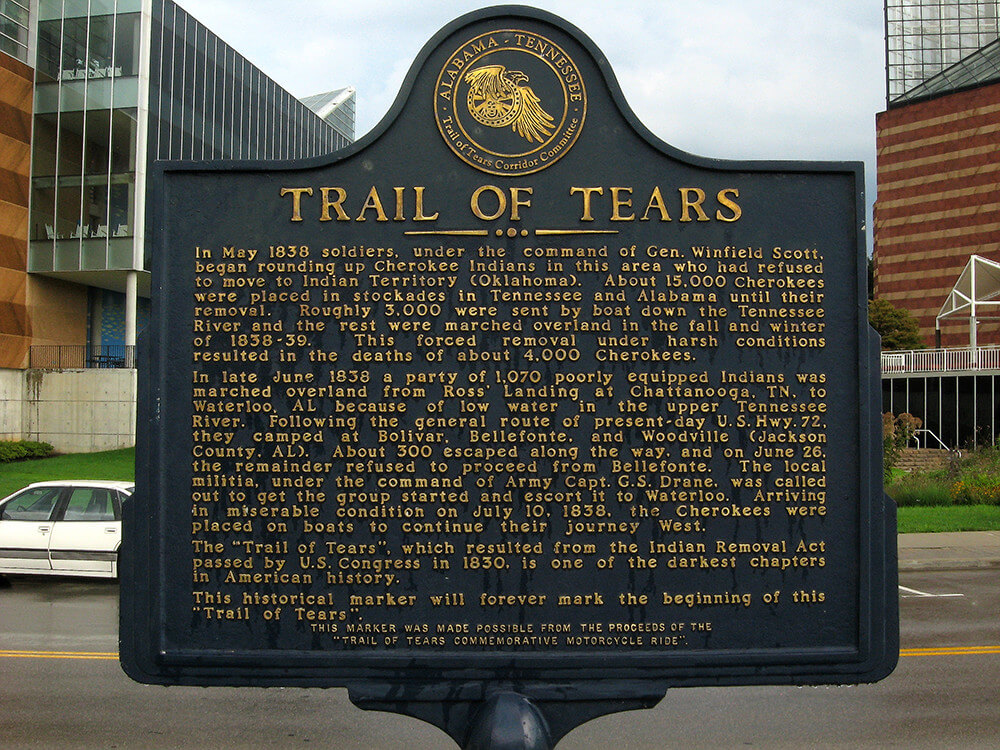 Photograph of the Trail of Tears historical marker, which describes the history of the trail of tears in golden text embossed on a black background.