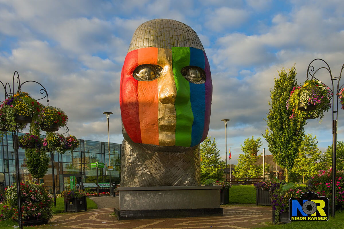Photograph of a large golden statue of a head with a rainbow striped mask over the face.