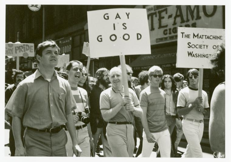 "Black and white photograph of men and women marching with signs reading ""Gay is good"" and ""Mattachine Society."""