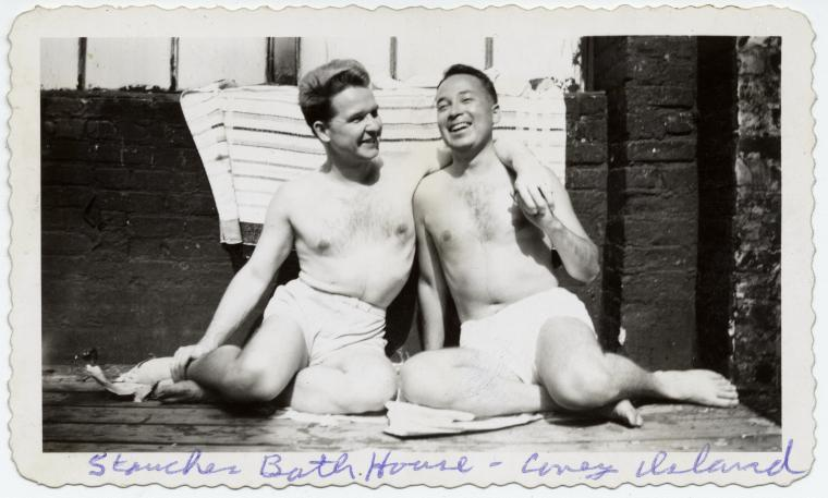 Black and white photo of two smiling men in swimming trunks, one's arm around the other