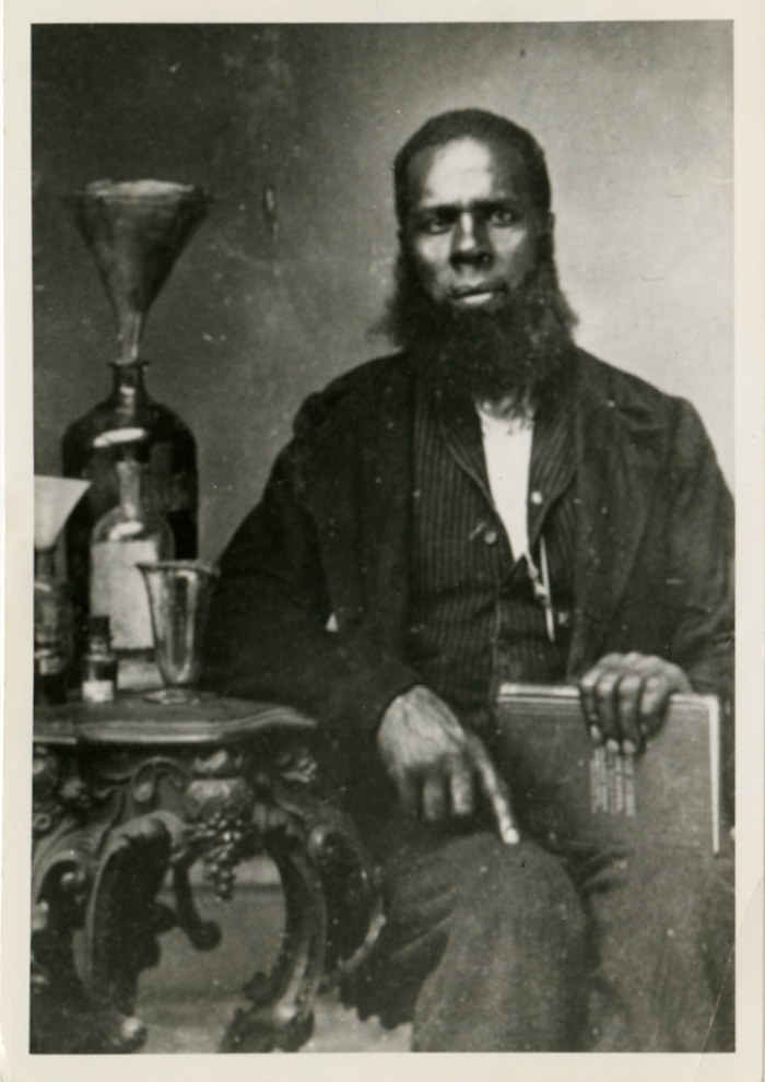 Black and white photograph of Joshua McCarter Simpson holding a book.