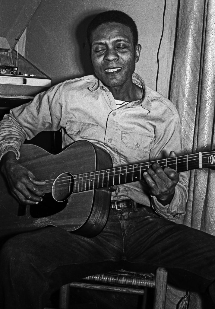 George Henry Bussey holding a guitar and singing with a smile.