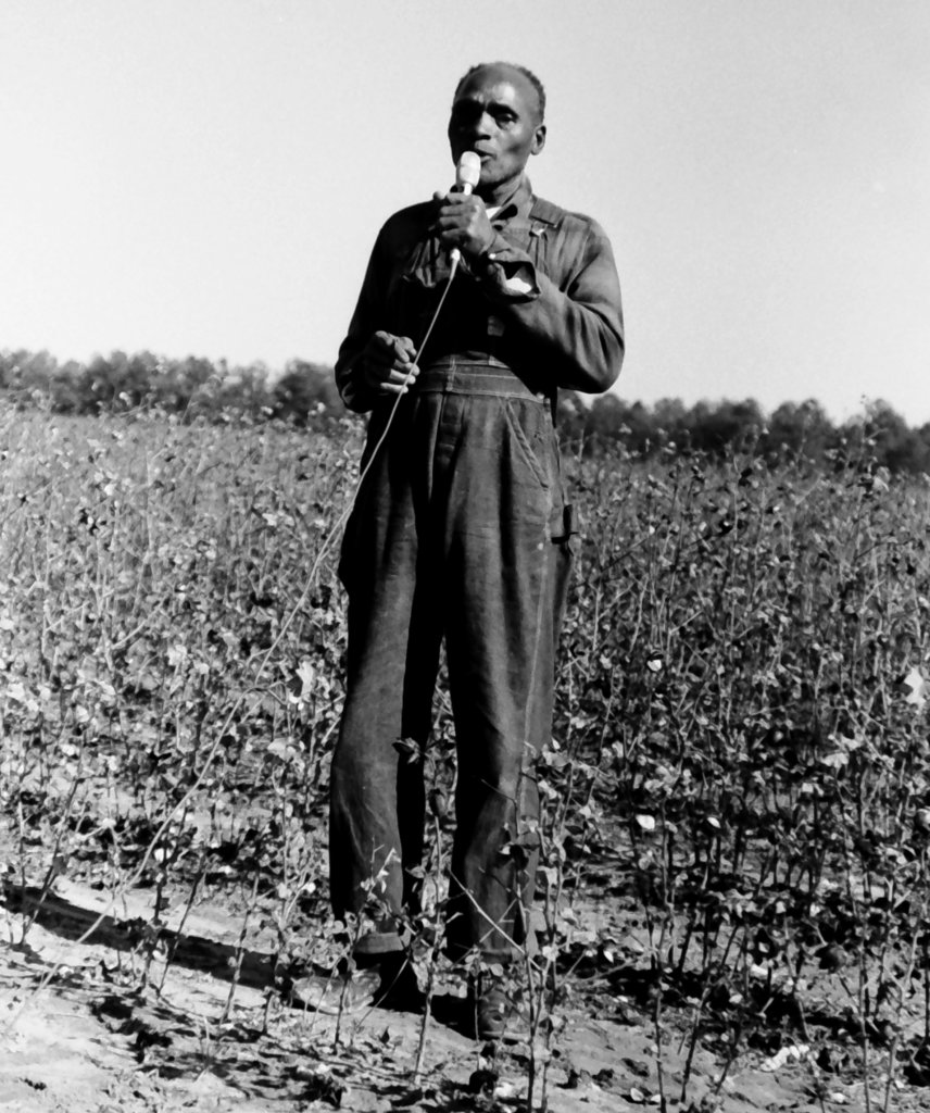Cliff Davis singing in a field, holding a microphone.