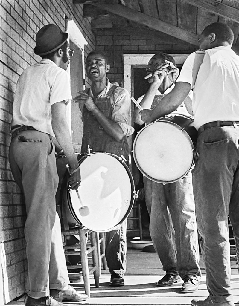 Four musicians on a porch, one singing, two playing snare drums, and one playing a flute.