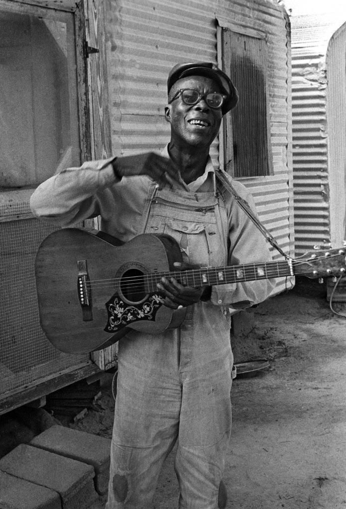 Lonzie Thomas holding a guitar.