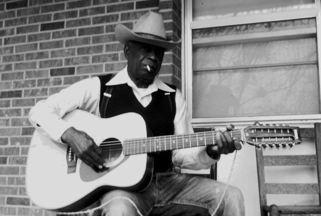 J. W. Warren playing the guitar.