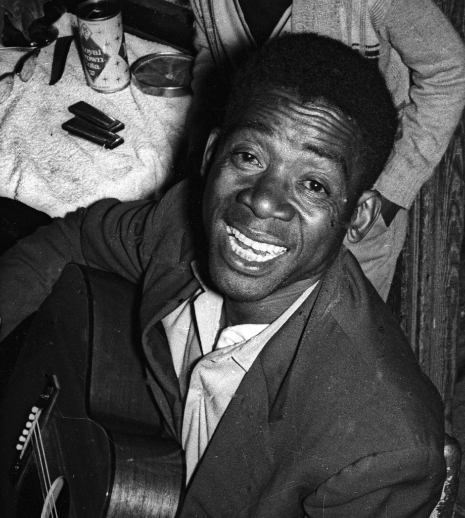 Bud White holding a guitar, smiling or singing, looking up at the camera.