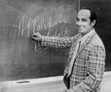 "Jim Wayne Miller writes ""Appalachian Literature"" on a chalkboard, smiling back at the camera."