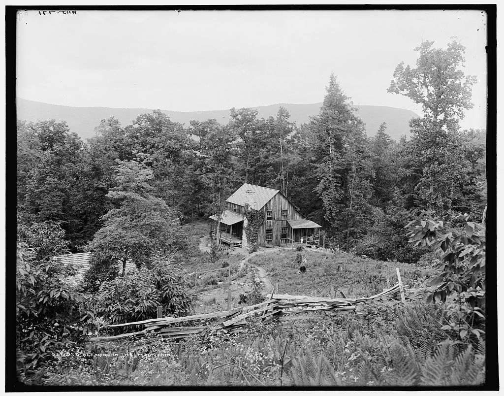 Black and white photograph of a wooden house in a clearing in the mountains behind an old wooden fence.