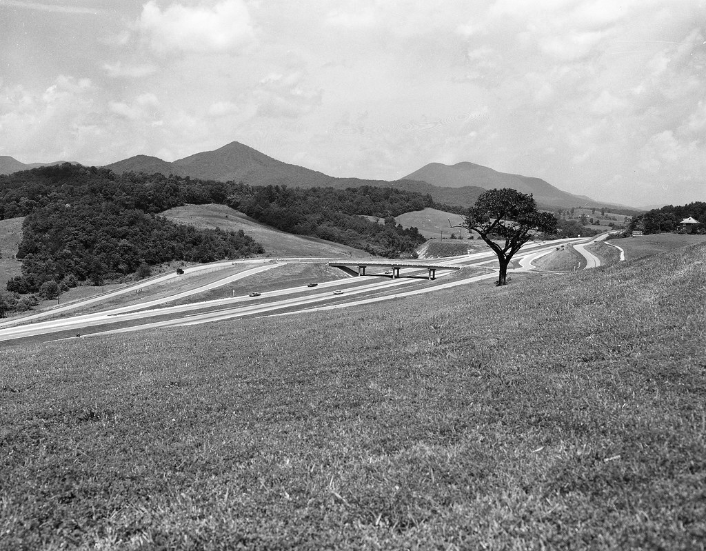 Black and white photograph of an interstate with rolling mountains in the background.