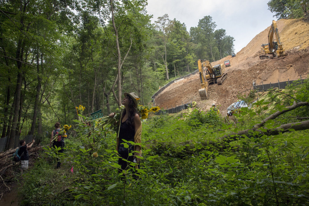 Laney Sullivan and other protestors stand in a forested area with bulldozers and developed land behind them.