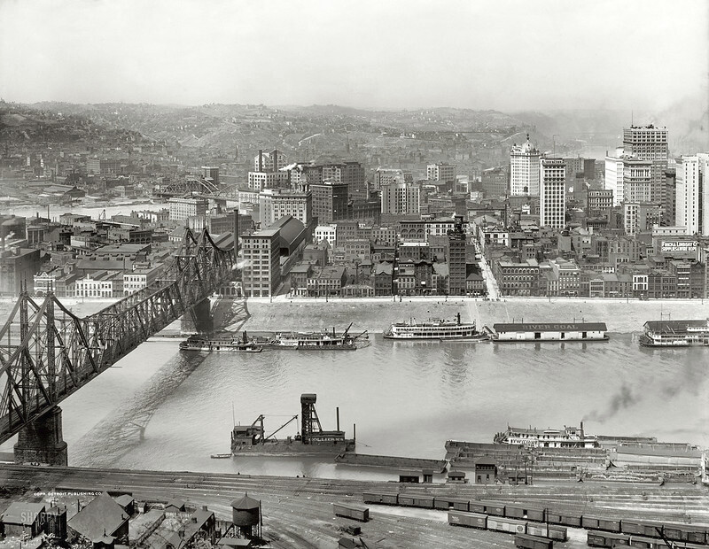 Black and white photograph of Wabash Bridge, showing boats and liners on the river in a circa 1908 industrial cityscape.