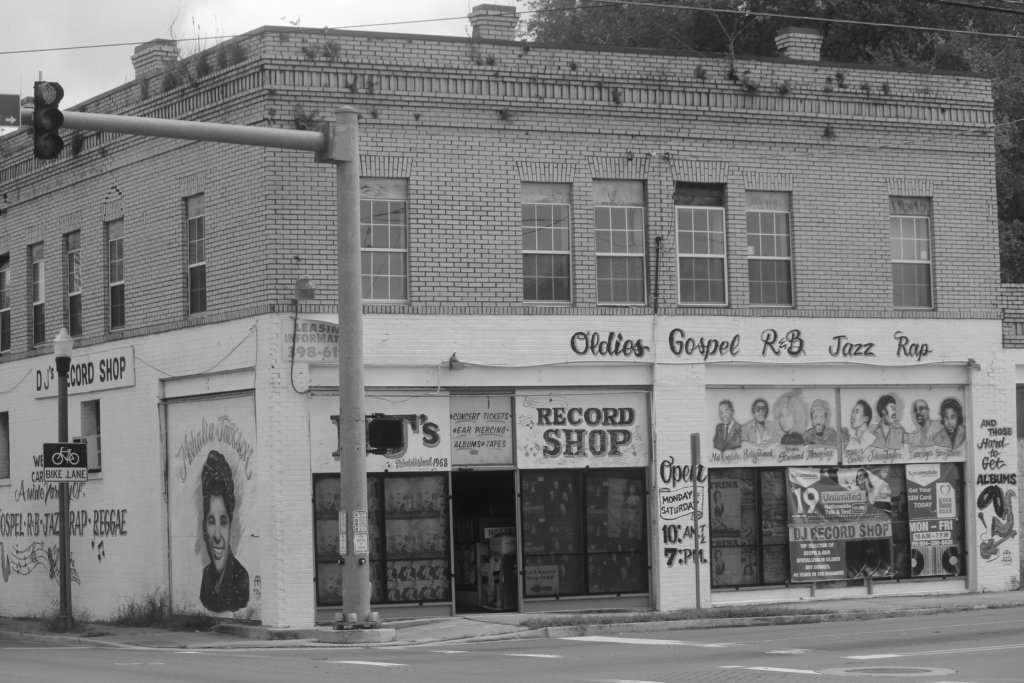 """Black and white photograph of storefront of DJ's Record Shop. The words """"Oldies,"""" """"Gospel,"""" """"R&B,"""" and """"Rap"""" are painted in cursive on the building."""